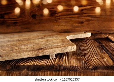 Empty wooden cutting board on rustic wooden table with golden bokeh for a decoration