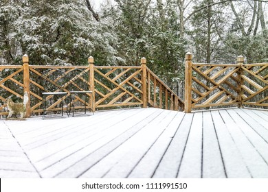Empty wooden deck of house with statue decorations, chairs, staircase down on backyard in neighborhood with snow covered wood floor during blizzard white storm, snowflakes falling in Virginia suburb