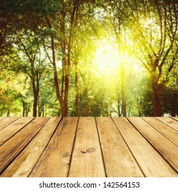 Empty wooden deck table over forest background