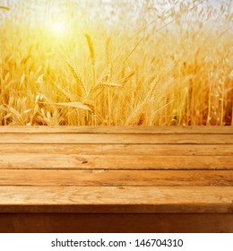 Empty wooden deck table over wheat field with sunset or sunrise. Ready for product montage