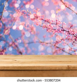 Empty wooden deck table over blurred bokeh spring garden background for product montage display