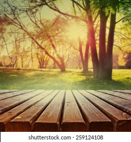Empty wooden deck table with park scenery background. Ready for product display montage.