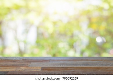 Empty wooden desk of free space and spring time with blurred background of home garden for a catering or food background,Template mock up for display montages of product.