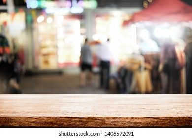 Empty wooden desk space and blurry background of street night market for product display montage