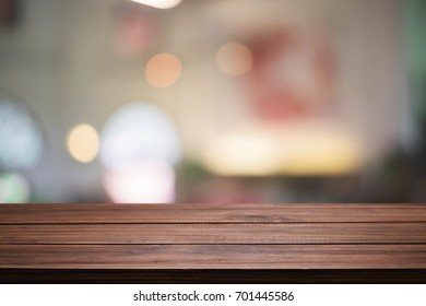Empty wooden desk space and blurry background of restaurant vintage tone for product display montage.