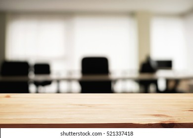 Empty wooden desk space over blurred office or meeting room background. Product display.