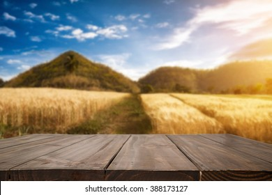 Empty of wooden desk space platform and agricultural field blue sky on background for product presentation.
