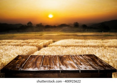 Empty of wooden desk space platform and barley agricultural field with sunset on background for product presentation.