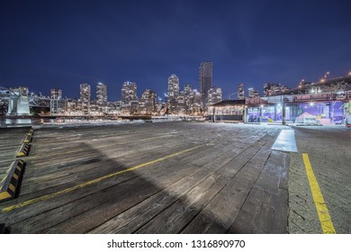 empty wooden dock with skyline background at night, vancouver, canada.