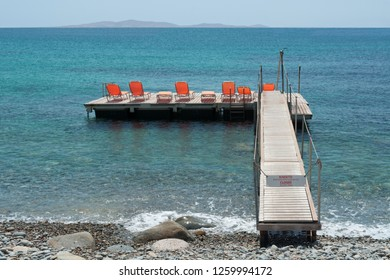 Empty wooden floating sun deck with orange sunchairs into the sea