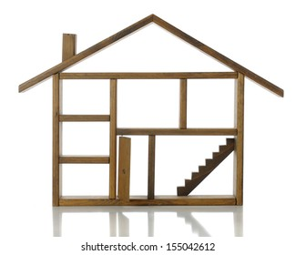 An empty wooden frame of a house showing rooms, chimney, door and stairs. On a white background.