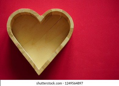 empty wooden heart box lie on red background. empty copy space for inscription. happy Valentines day.