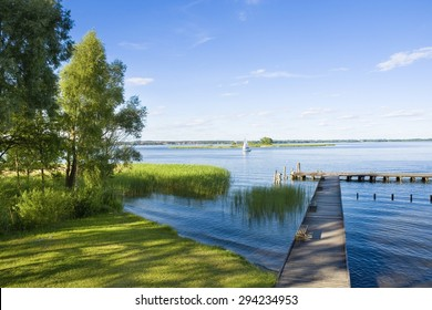 Empty wooden jetty on the lake shore with island and yachts in the background, Niegocin Lake, Mazury, Poland