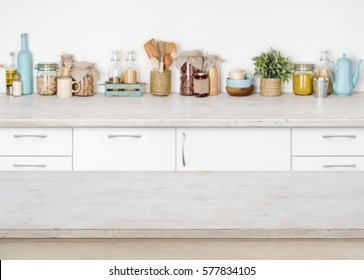 Empty wooden kitchen table on blurred background of food ingredients.