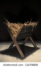 An empty wooden manger filled with hay.