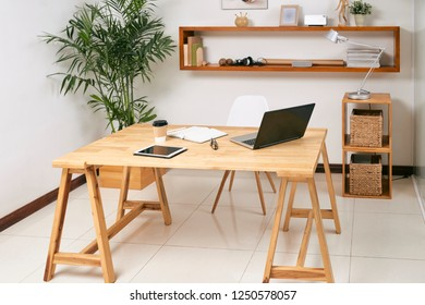 Empty wooden office table with laptop, touchpad and notepad on it with green plant and big shelf in the background