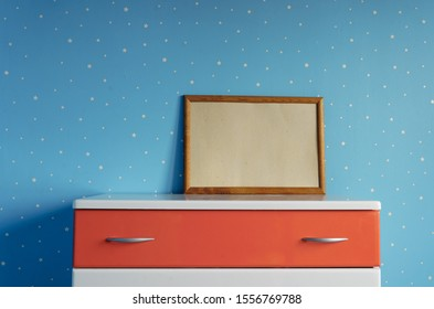 empty wooden photo frame on the dresser in the blue star children's room. Mockup image