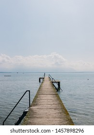 Empty wooden pier against blue lake Chiemsee during sunny morning
