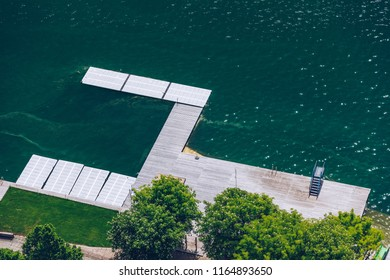 Empty wooden pier close to Bled lake, swimming area of the Bled lake under the sunny sky. Platform beside lake. Wooden pier on the lake. Bled, Slovenia