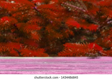 Empty wooden pink table on red christmas trees background, space with artboard