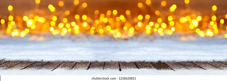 empty wooden planks floor on christmas snow in front of bright lights golden warm bokeh wide panorama christmas background
