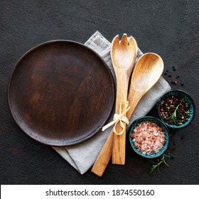 Empty wooden plate on a black background