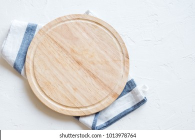 Empty wooden platter with napkin on white stone table, top view, copy space. Wooden cutting board over white concrete background.