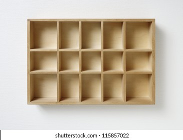 Empty wooden rack on white wall