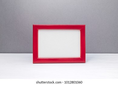 empty wooden red photo frame on grey wall background. minimalism design.
