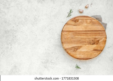Empty wooden round board on white stone kitchen table, top view, flat lay. Wooden pizza platter, copy space.