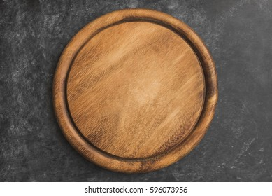 Empty wooden round platter on black background.Top view, copy space.