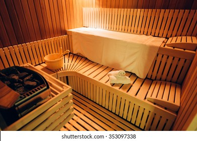 Empty wooden sauna room with towels, ladle, bucket ready to be used