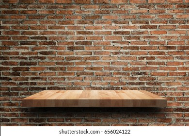 Empty wooden shelf on old brick wall texture. For display or montage your products with focus wooden shelf top in the foreground. Empty wooden brown shelf. shelves