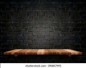 Empty wooden shelf on pastel grunge black brick wall, Mock up template for display of product