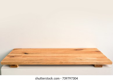 Empty wooden shelf on a white wall, backdrop ready to use for display or montage of your products