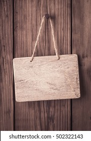 Empty wooden signboard with rope hanging on old wooden background