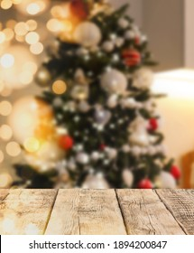 Empty wooden surface and blurred view of Christmas tree in room, space for text. Interior design