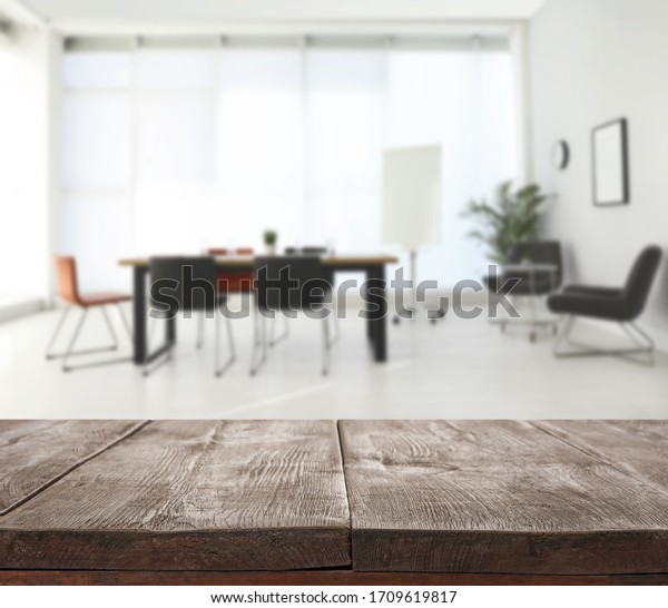 Empty wooden surface and blurred view of modern office interior, closeup. Space for text