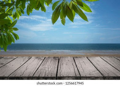 Empty wooden surface with green tropical broad leaves and beautiful beach in background. For product montage.