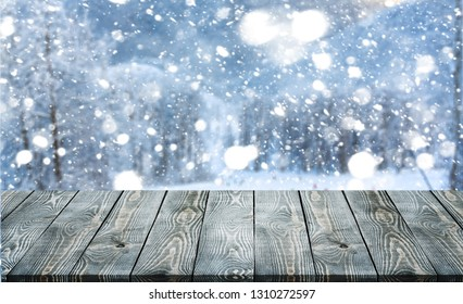 Empty wooden surface for product montage with falling snow and nice view of Christmas trees in winter time.