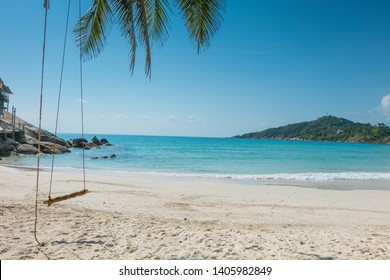 Empty wooden swing on an exotic beach - Phangan island, Thailand. Wodden swing tied with ropes to a tree with sea and beach in the background.