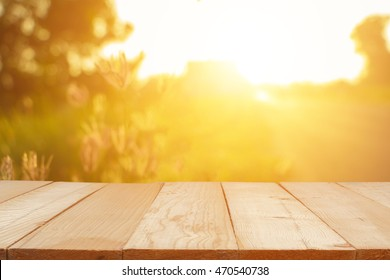 Empty wooden table with autumn for a catering or food background with a country outdoor theme,Template mock up for display of product,Blurred grass in bright morning.