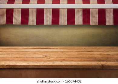 Empty wooden table with awning background. Ready for product montage display.