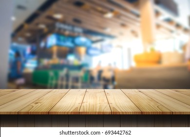 Empty wooden table and Blur coffee shop or cafe restaurant for product placement.