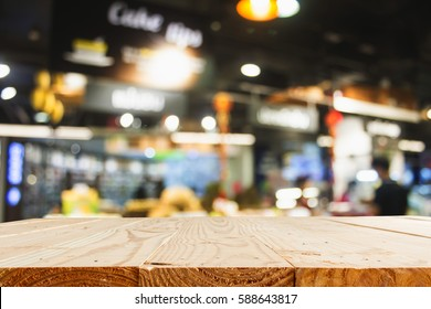 empty wooden table and blur department store with bokeh for background - template for product display montage and business presentation
