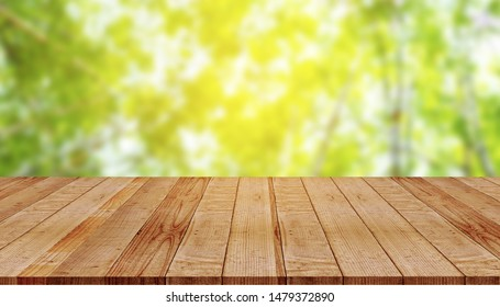 Empty wooden table with blur of green nature background
