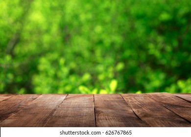 Empty wooden table with blur green leaves bokeh background for product display montage