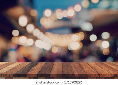 Empty wooden table and blurred background at night market festival people walking on road with copy space, display montage for product.