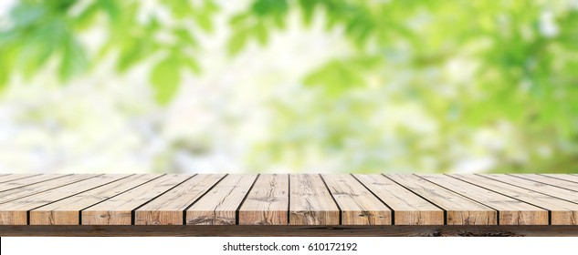 Empty wooden table with blurred green background with a country outdoor theme / Template mock up for display of product