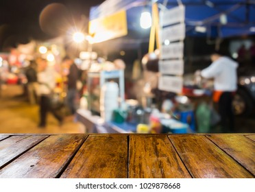 empty wooden table and blurred image of noodle shop on the street market in the country of Thailand